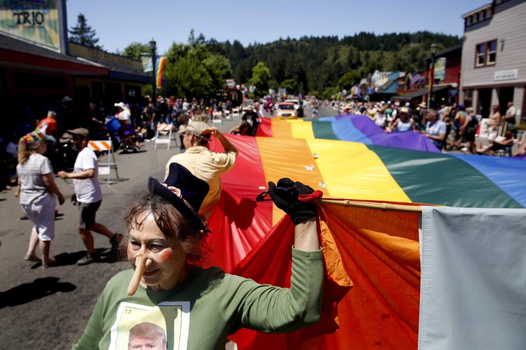 Jackie Mendoza carries a pride flag with a group from Food For Thought during the Sonoma County Gay Pride Parade in Guerneville, on Sunday, June 5, 2016. (BETH SCHLANKER/ The Press Democrat)