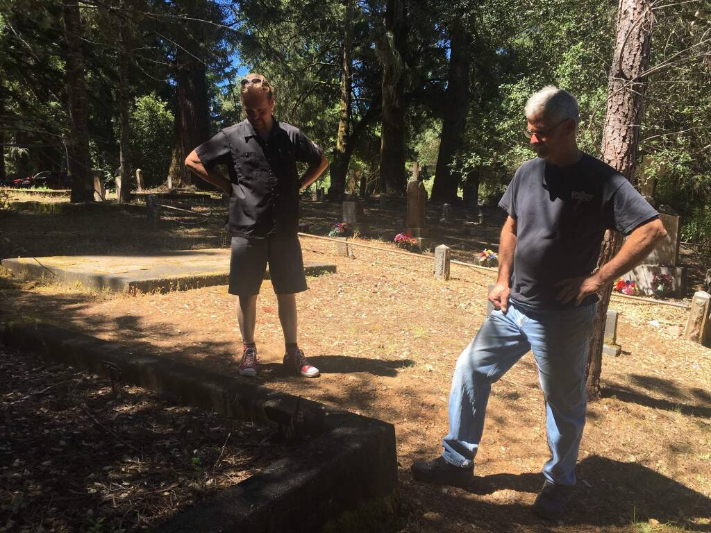 """At left, Petri """"Pete"""" Niskanen of Finland, a distant relative of Titanic survivor Juho """"John"""" Niskanen examines graves July 15 in the Guerneville cemetery where his ancestor was buried in 1927. At right is Paul Barry of the Russian River Historical Society. (Chris Smith)"""
