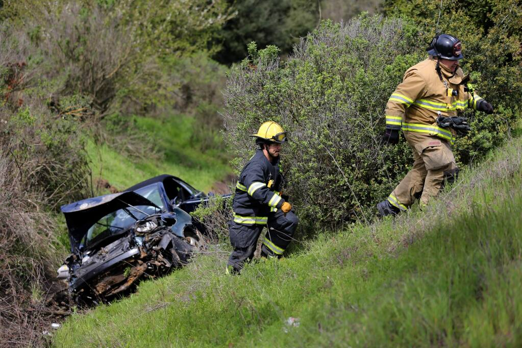 Rancho Adobe firefighters work at the scene of a crash after a car went down an embankment off southbound Highway 101 in Cotati, California, on Sunday, March 24, 2019. (RAMIN RAHIMIAN/ FOR PD)