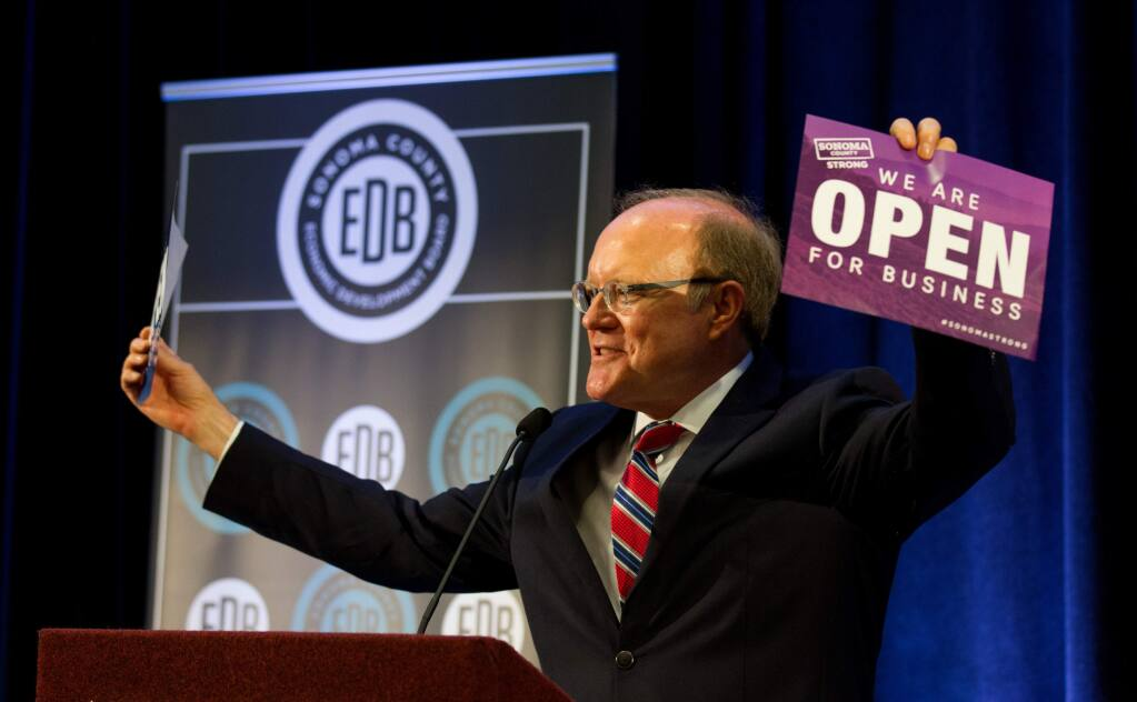 Ben Stone, Executive Director of Sonoma County Economic Development Board, holds up a sign that says 'We Are Open For Business' at the Fall Economic Forecast meeting for Sonoma County Economic Development Board, at the Hyatt Regency in Santa Rosa, on Friday, November 17, 2017. (Photo by Darryl Bush / For The Press Democrat)
