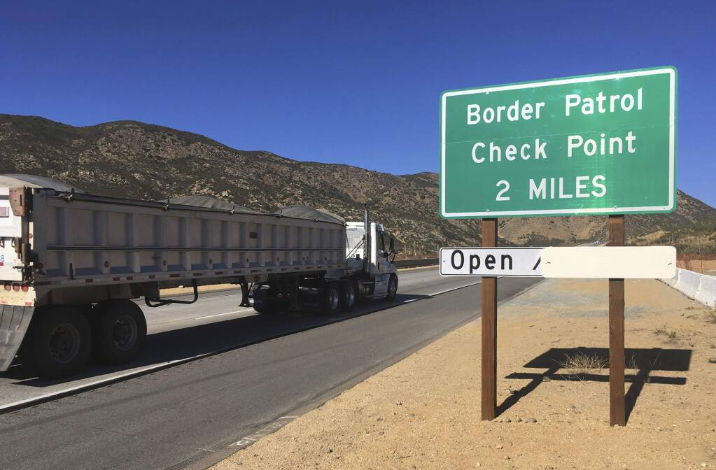 In this Thursday, Dec. 14, 2017 photo, a sign warns of the upcoming California Pine Valley checkpoint, on the main route from Arizona to San Diego. California legalizes marijuana for recreational use Jan. 1 but that won't stop federal agents from seizing small amounts on busy freeways and backcountry highways. Possession will still be prohibited at eight Border Patrol checkpoints in California, a daily demonstration of state and federal law colliding. (AP Photo/Elliot Spagat)
