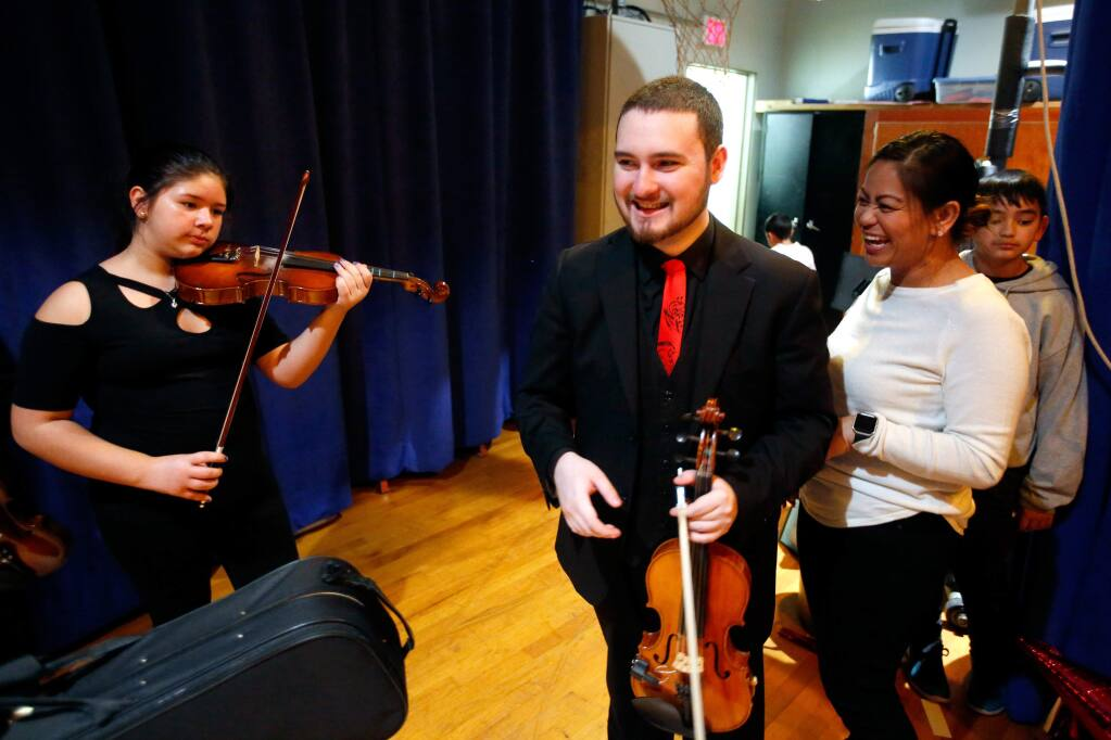 Violin teacher Victor Vasquez, center, chats with chorus teacher Dawn Moore, second from right, before Vasquez's fifth and sixth grade violin class performs at Bellevue Elementary School's Winter Wonderland festival, in Santa Rosa, California, on Tuesday, December 18, 2018. (Alvin Jornada / The Press Democrat)
