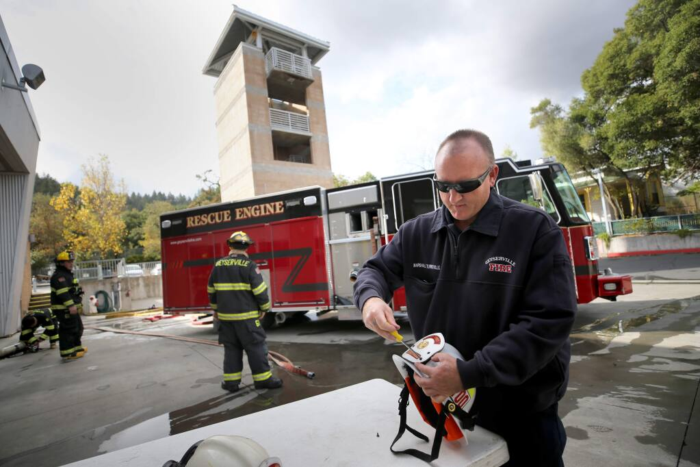 Geyserville Fire Protection District Chief Marshall Turbeville attaches a fire chief badge that belonged to his late father to his new helmet at the fire station in Geyserville on Wednesday, November 27, 2019. (BETH SCHLANKER/ The Press Democrat)
