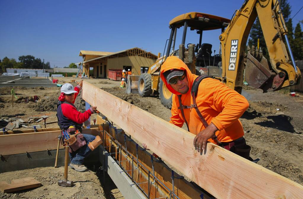 Jesus Angel, left, and Manuel Guzman work on the Ortiz Family Plaza, which will include 30 affordable housing units, in the Larkfield area, on Tuesday, September 6, 2016. (Christopher Chung/ The Press Democrat)