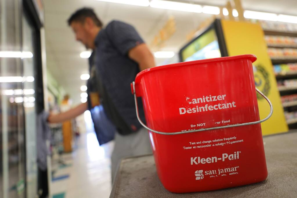 Front end manager Greg Goben, uses a disinfectant to wipe down surfaces that are frequently touched by customers at Community Market, in Santa Rosa on Thursday, March 12, 2020. (Christopher Chung/ The Press Democrat)