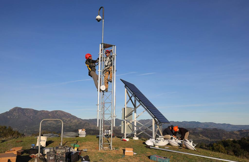 Sara Meyer, left, a field technician from the University of Oregon, and Will Honjas, a field operations coordinator at the Nevada Seismological Laboratory, install an Alert Wildfire camera onto a tower at Pepperwood Preserve, near Santa Rosa, on Tuesday, January 22, 2019. (Christopher Chung/ The Press Democrat)