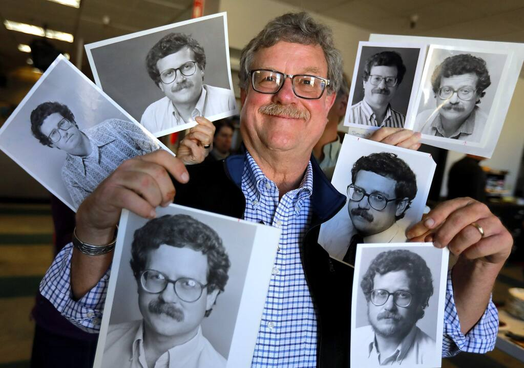 Newsroom colleagues stand behind Chris Smith in the PD newsroom in 2018 and hold some of the photos taken of him throughout his more than 40 years of writing for the paper. (John Burgess/The Press Democrat)