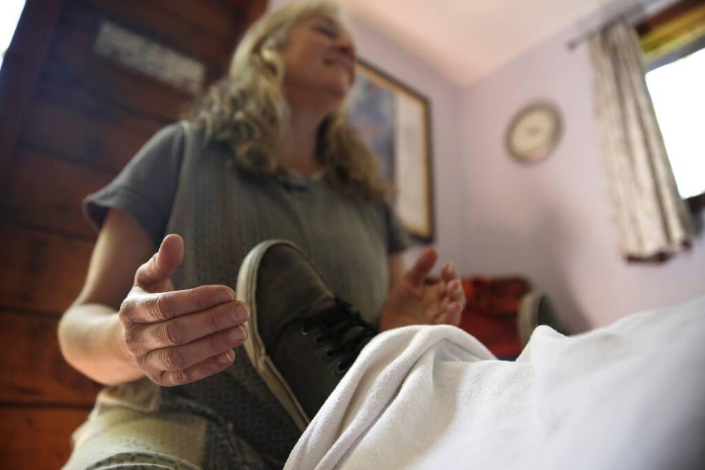 -Pam Rowen-Herzog, a spiritual midwife, treats Jeremiah Becker, 12, at her home office in Cotati.