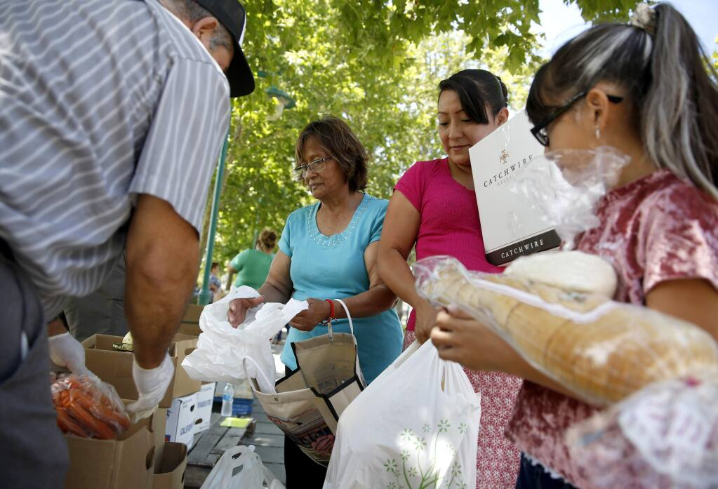 (From right) Anahi Hernandez, 8, her mother Maria Camacho, and grandmother Magda Huerta fill their bags with food donated through the Redwood Empire Food Bank's Station 3990 program at Martin Luther King Jr. Park in Sonoma on Thursday, July 12, 2018. (Beth Schlanker/ The Press Democrat)