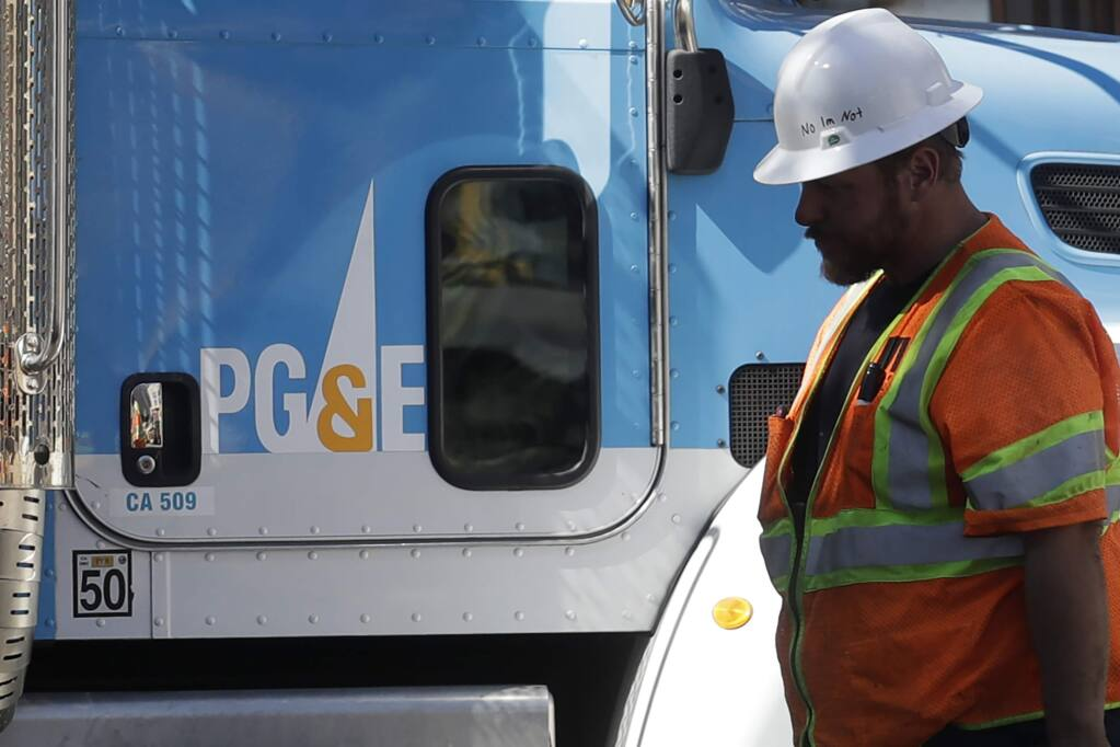 FILE -- In this Aug. 15,2019 file photo a Pacific Gas & Electric worker walks in front of a truck in San Francisco. (AP Photo/Jeff Chiu, File)