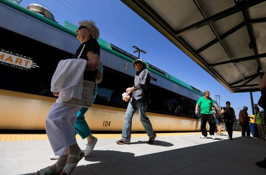 Passengers use the Airport Boulevard SMART platform to catch the first regularly scheduled train on Friday, Aug. 25, 2017 in Santa Rosa. (KENT PORTER/The Press Democrat)