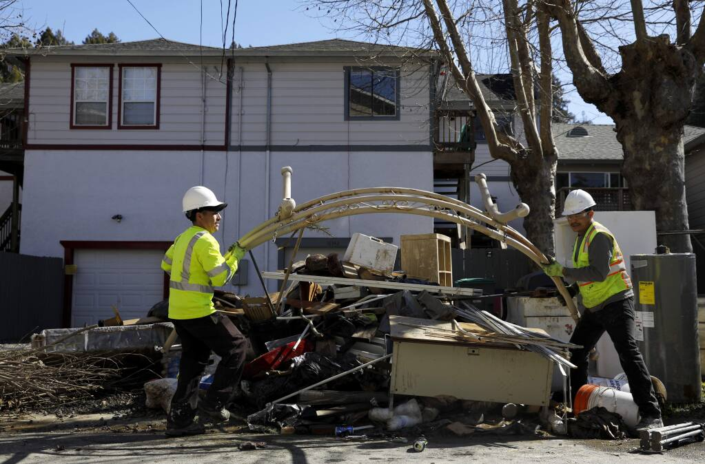 Antonio Zuniga, left, and Geraldo Lemus, employees with Pacific Sanitation work to dispose of water damaged belongings and debris along the sidewalk in Guerneville on Monday, March 11, 2019. (BETH SCHLANKER/ The Press Democrat)