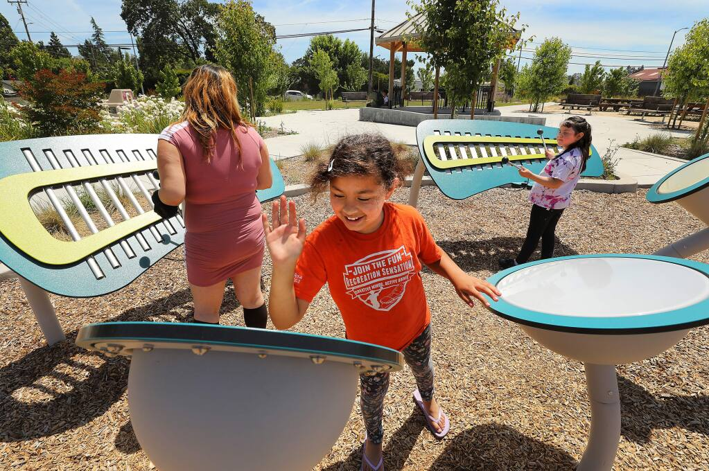 From left, Juanita Tlahuitzo plays instruments with her daughters Illyanna, 9, and Mercedes, 7, at Andy's Unity Park in southwest Santa Rosa on Wednesday. The Board of Supervisors banned the use of insecticides in county playgrounds plazas and parks. (photo by John Burgess/The Press Democrat)