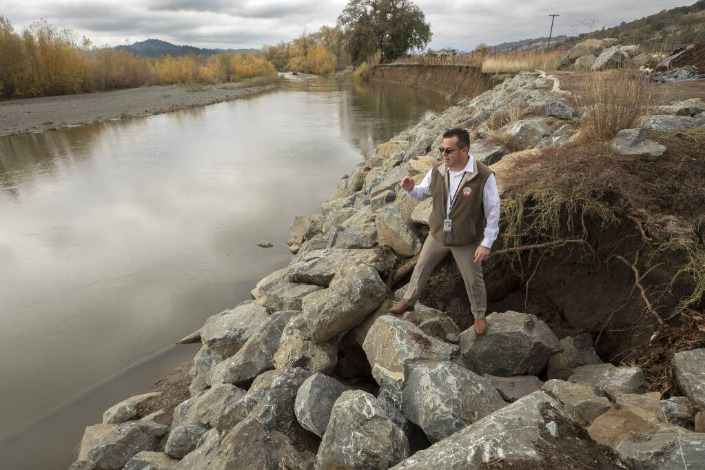 Sonoma County Director of Transportation & Public Works, Johannes Hoevertsz stands on a wall of erosion control rocks on the Russian River near Geyserville. Gravel has shifted the Russian River taking out portions of a vineyard and threatening damage to River Rd. (photo by John Burgess/The Press Democrat)