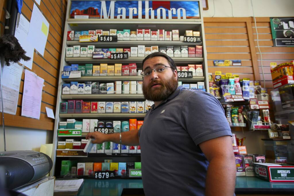 Aman Gill grabs a pack of cigarettes for a customer at his family's Fast Lane gas station, in Healdsburg, on Tuesday, June 30, 2015. (Christopher Chung / The Press Democrat)