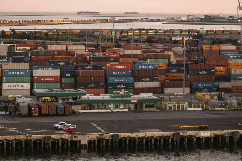 A tiny boat pulls up to a container ship being loaded at the Port of Seattle, Monday, Feb. 9, 2015, in Seattle. West Coast seaports fully reopened Monday after two days during which no ships were unloaded amid a labor dispute between dockworkers and their employers. The two sides are negotiating a new contract, and bargaining-table tensions have spilled over to the waterfront, where cargo is moving far slower than normal through ports that handle about one-quarter of the nation's international trade nearly $1 trillion annually. (AP Photo/Elaine Thompson)