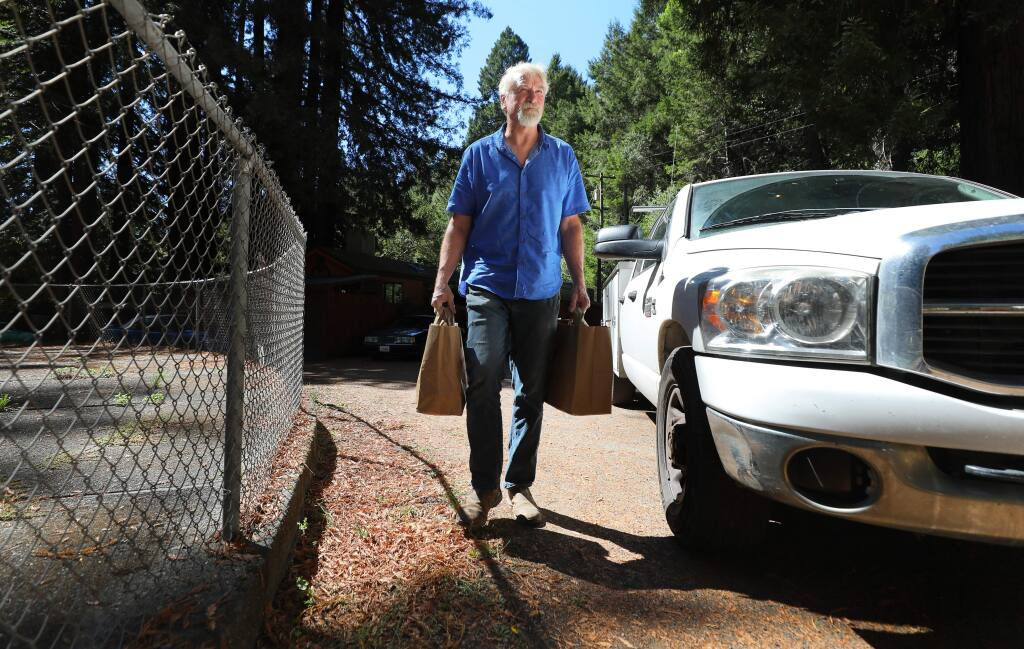 Hunter Smith delivers groceries to a Food For Thought client in Guerneville on Tuesday, September 24, 2019. (Christopher Chung/ The Press Democrat)