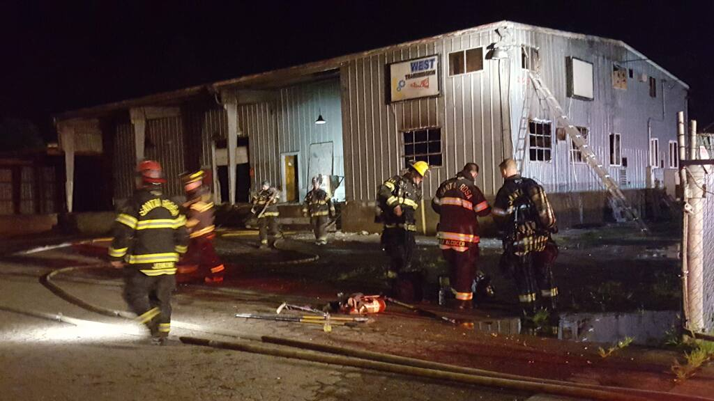 Santa Rosa firefighters at the scene of a fire inside an abandoned metal building in the 200 block of Roseland Avenue on Saturday, March 26, 2016. (ELOÍSA RUANO GONZÁLEZ/ PD)