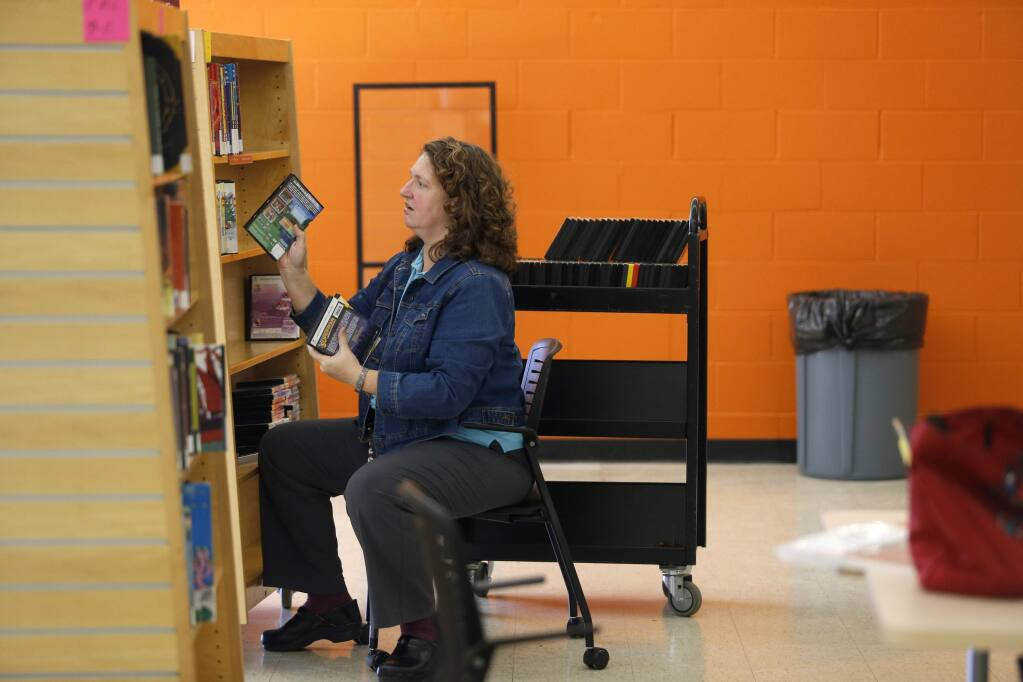 Kathy DeWeese, the coordinator of Children's Services for the Sonoma County Library System, puts DVDs on the shelves before the Roseland Community Library opened in 2015. (BETH SCHLANKER / The Press Democrat)