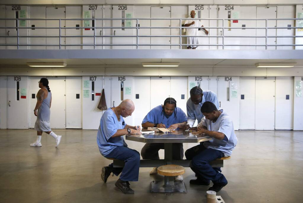 (From left) Inmates Gary Adams, Poyer Vaenuku, Ray Jackson, and Anthony Valles, part of the Artists Serving Humanity group, decorate paper luminary bags to be used for the Sonoma Relay for Life. Photo taken at California State Prison, Solano on Thursday, August 4, 2016 in Vacaville, California . (BETH SCHLANKER/ The Press Democrat)