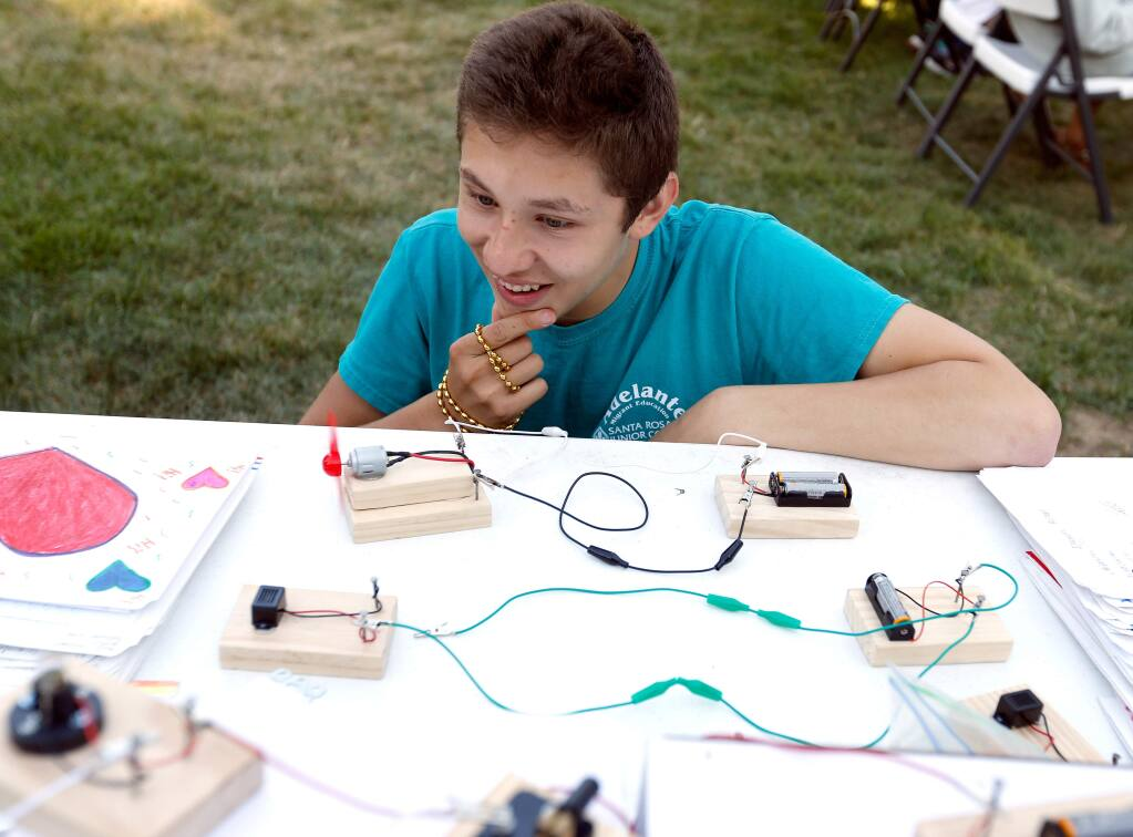 Alejandro Cardenas, 16, who is in his third summer participating in the Adelante program, ponders how to connect a series of battery-powered electric motors during parents night for students of the Adelante Migrant Education summer program at Santa Rosa Junior College in Santa Rosa, California, on Wednesday, July 18, 2018. (Alvin Jornada / The Press Democrat)