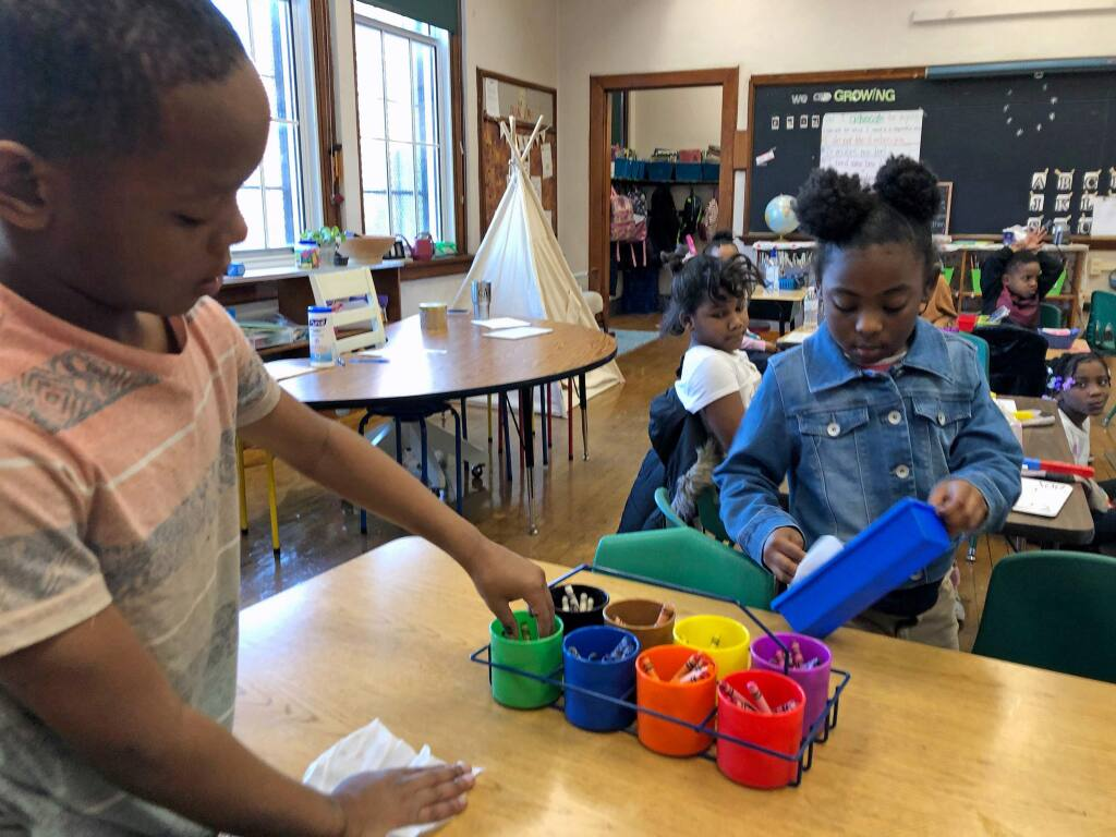 First graders Anthony Chatman, left, and Malaysia Freeman wipe down a play table and items on it with hand wipes at Patrick Henry Elementary School in St. Louis on Tuesday, March 3, 2020. The school district, amid Coronavirus concerns, last week purchased hand wipes and sanitary soap for every classroom. (AP Photo/Jim Salter)