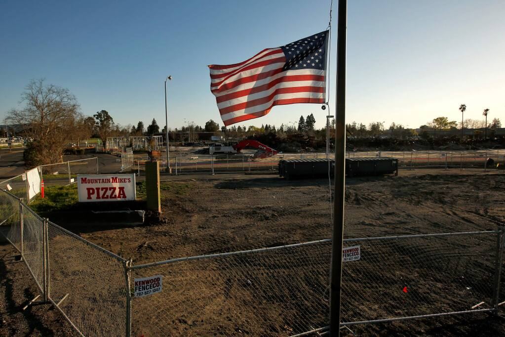 An American flag flies at half staff above the cleared property that was the location of Mountain Mike's Pizza, with what remains of K-mart in the background, on Cleveland Avenue in Santa Rosa, California, on Wednesday, February 21, 2018. Both businesses were destroyed during the Tubbs fire in October 2017. (Alvin Jornada / The Press Democrat)