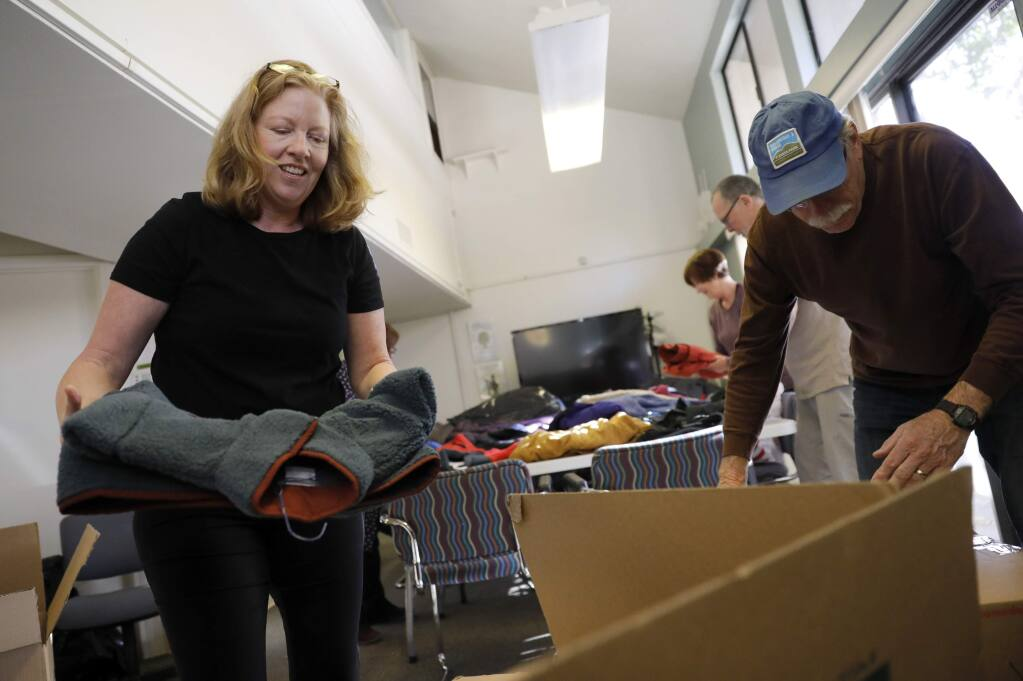 Volunteers Denise Rose, left, and Bob Crozier box up coats to be sent to Chico, Ca. at the Jewish Community Center, Sonoma County in Santa Rosa on Thursday, December 6, 2018. (BETH SCHLANKER/ The Press Democrat)