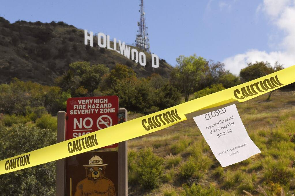 A sign is seen at the entrance to Innsdale Trail near the Hollywood Sign, Saturday, March 28, 2020, in Los Angeles. With cases of coronavirus surging and the death toll surpassing 100, lawmakers are pleading with cooped-up Californians to spend a second weekend at home to slow the spread of the infections. It has been more than a week since Gov. Gavin Newsom barred 40 million residents from going outdoors except for essentials. Even so, reports of crowds have prompted local and state officials to warn that ignoring social distancing, park and beach closures could spread the virus, which already is surging. (AP Photo/Mark J. Terrill)
