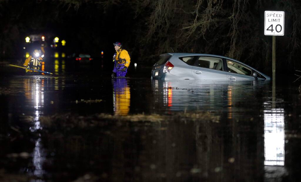 Santa Rosa Fire Department swift water rescue team members Capt. Wesley David, right, and firefighter Rob Giles check the area around a car stuck in the flood water on Willowside Road after rescuing its occupants, in Santa Rosa, California, on Wednesday, February 27, 2019. (Alvin Jornada / The Press Democrat)