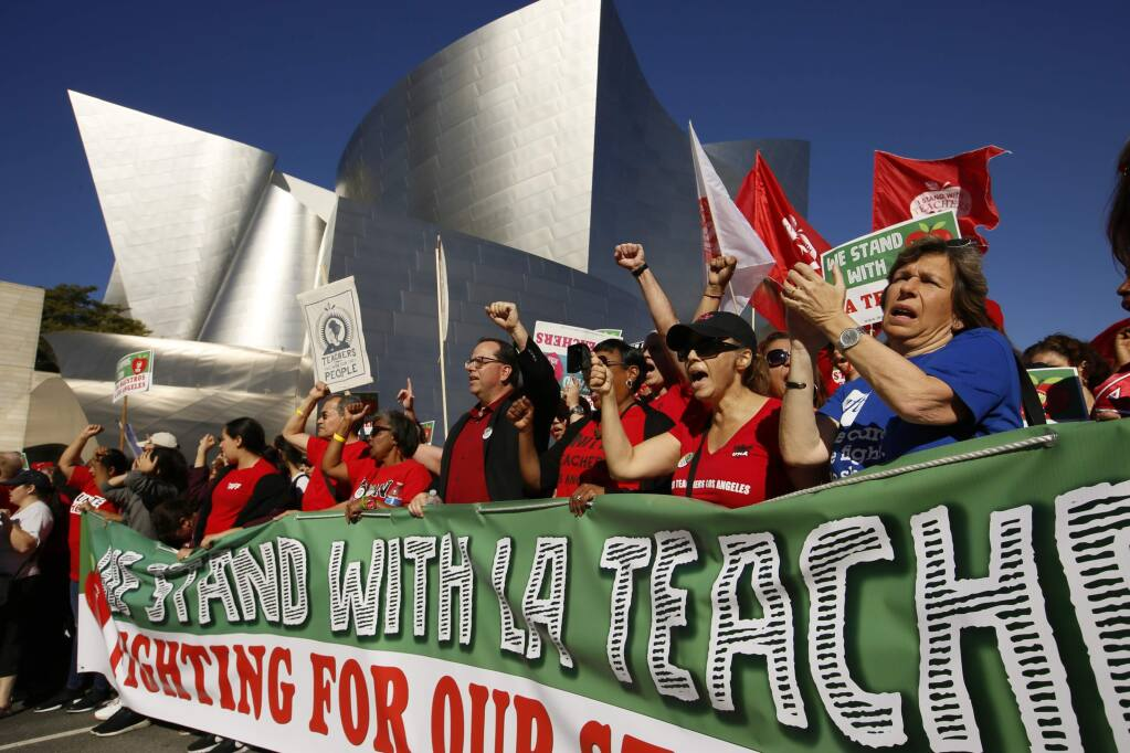 FILE - In this Dec. 15, 2018, file photo, United Teachers Los Angeles leaders are joined by thousands of teachers march past the Walt Disney Concert Hall in Los Angeles. Strike or no strike, after a deal is ultimately reached on a contract for Los Angeles teachers, the school district will still be on a collision course with deficit spending because of pensions and other financial obligations. School systems across California are experiencing burdensome payments to the state pension fund while struggling to improve schools. (AP Photo/Damian Dovarganes, File)
