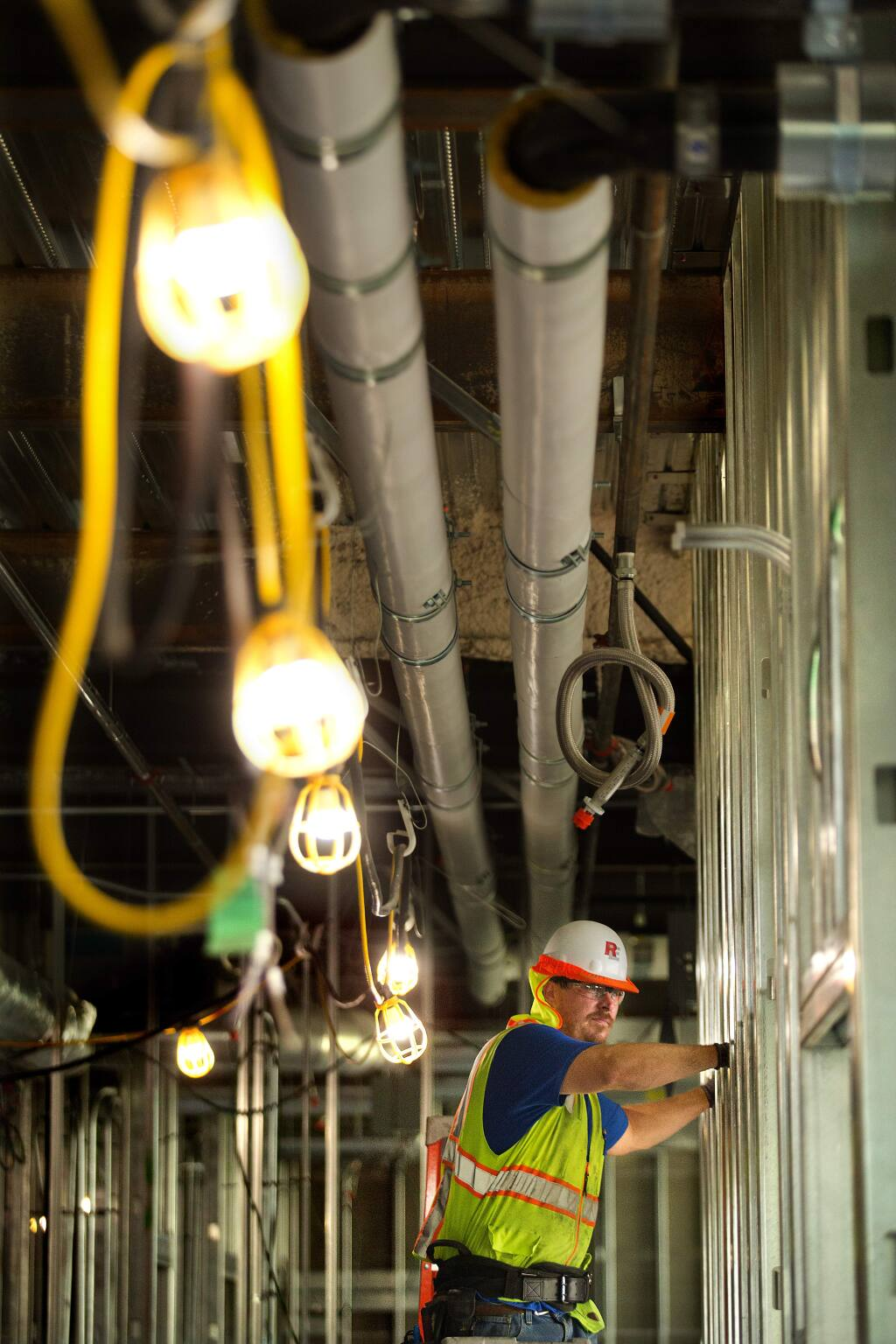 Electrician's apprentice Jon Dills runs wire through metal studs in a new Kaiser Permanente Medical Office building in Santa Rosa on Thursday. Dills will spend five years in the IBEW Local 551 apprentice program before becoming a journeyman. (photo by John Burgess/The Press Democrat)