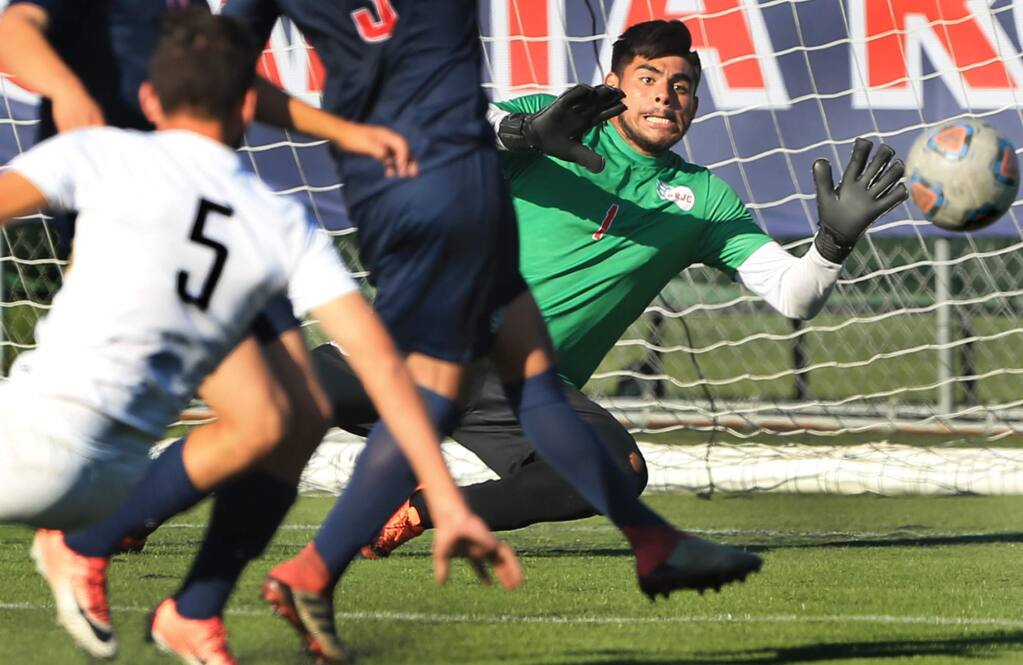 Santa Rosa goalkeeper Javier Aguilar makes a stop on goal from Miguel Millan, No. 5, of Delta College during the first-half Tuesday, Sept. 25, 2018, at Santa Rosa Junior College. (Kent Porter / Press Democrat)