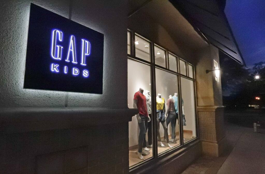 FILE - This Aug. 23, 2018, file photo shows a window display at a Gap Kids clothing store in Winter Park, Fla. Gap is being sued for refusing to pay rent for stores temporarily closed during the coronavirus pandemic. Mall owner Simon Property Group filed a lawsuit in early June 2020, claiming the clothing retailer owes three months of rent, totaling $65.9 million. (AP Photo/John Raoux, File)