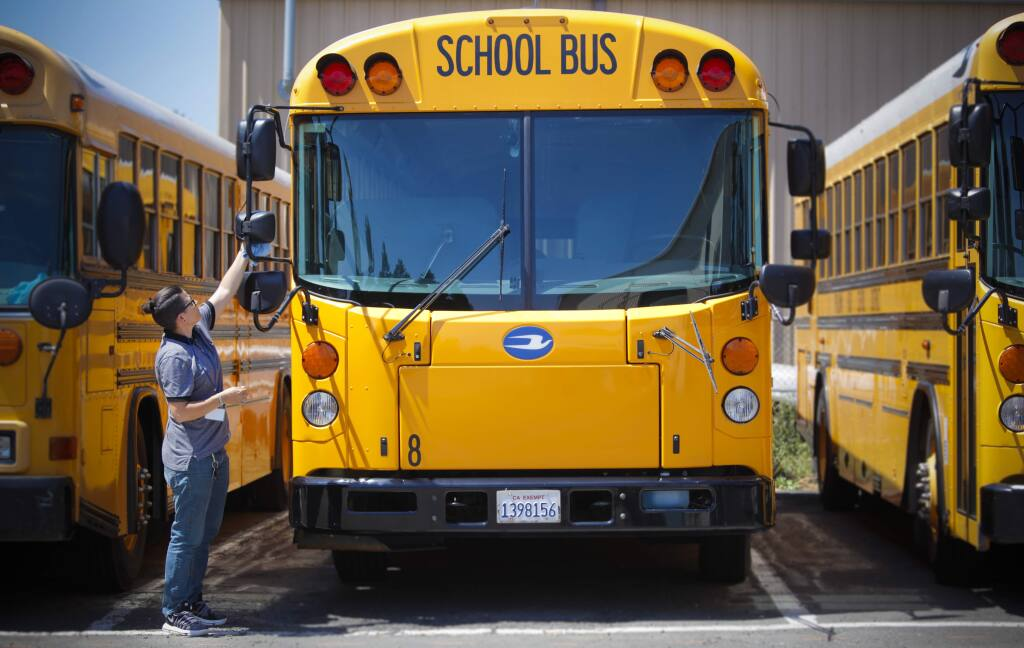 Petaluma, CA, USA. Tuesday, August 13, 2019._ Ashley Smith, a dispatcher and school bus driver for Petaluma City Schools Department of Transportation, prepares one of the school buses for the first day of school. (CRISSY PASCUAL/ARGUS-COURIER STAFF)