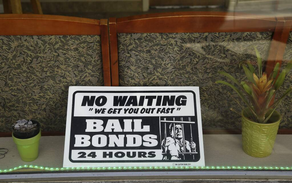 A sign is seen in the window of a bail bonds office across from the Hall of Justice in San Francisco. (ERIC RISBERG / Associated Press)