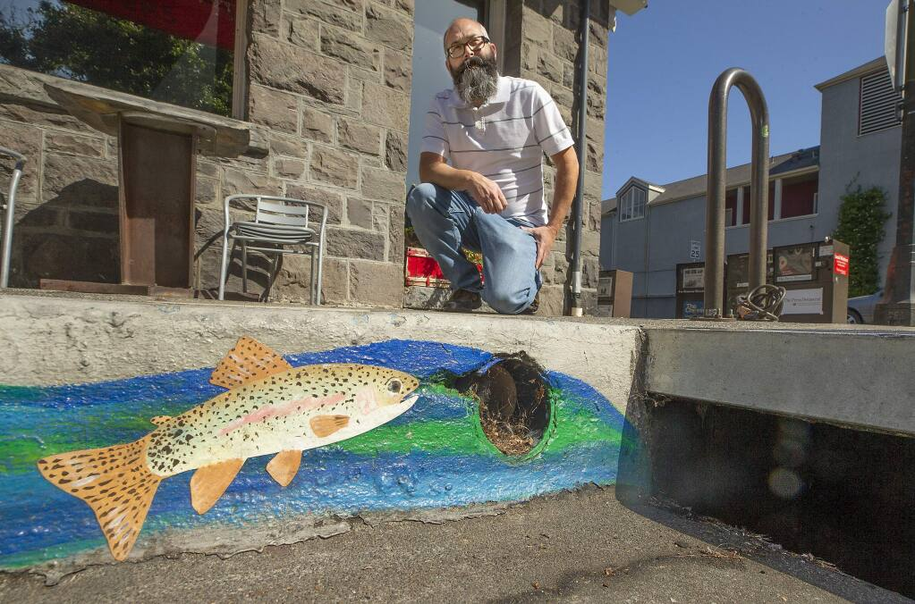 City of Santa Rosa senior environmental specialist Nick Sudano kneels next to a storm drain painted by the city to remind people that the drains ultimately flow into our creeks and ocean. (John Burgess/The Press Democrat)