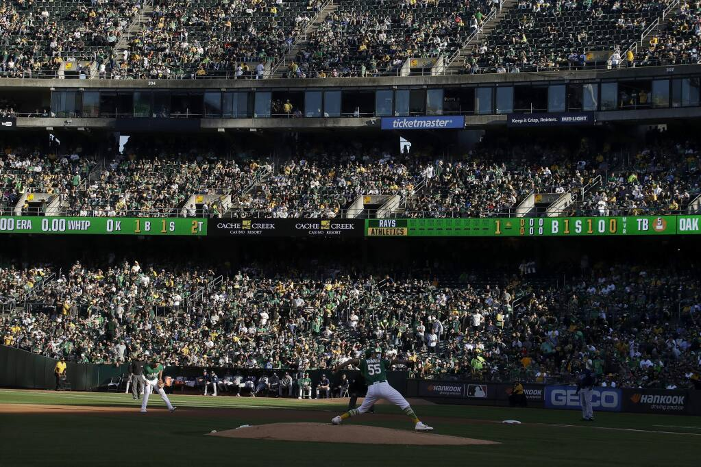 Fans at RingCentral Coliseum watch as Oakland Athletics pitcher Sean Manaea (55) throws to a Tampa Bay Rays batter during the first inning of an American League wild-card baseball game in Oakland, Calif., Wednesday, Oct. 2, 2019. (AP Photo/Jeff Chiu)