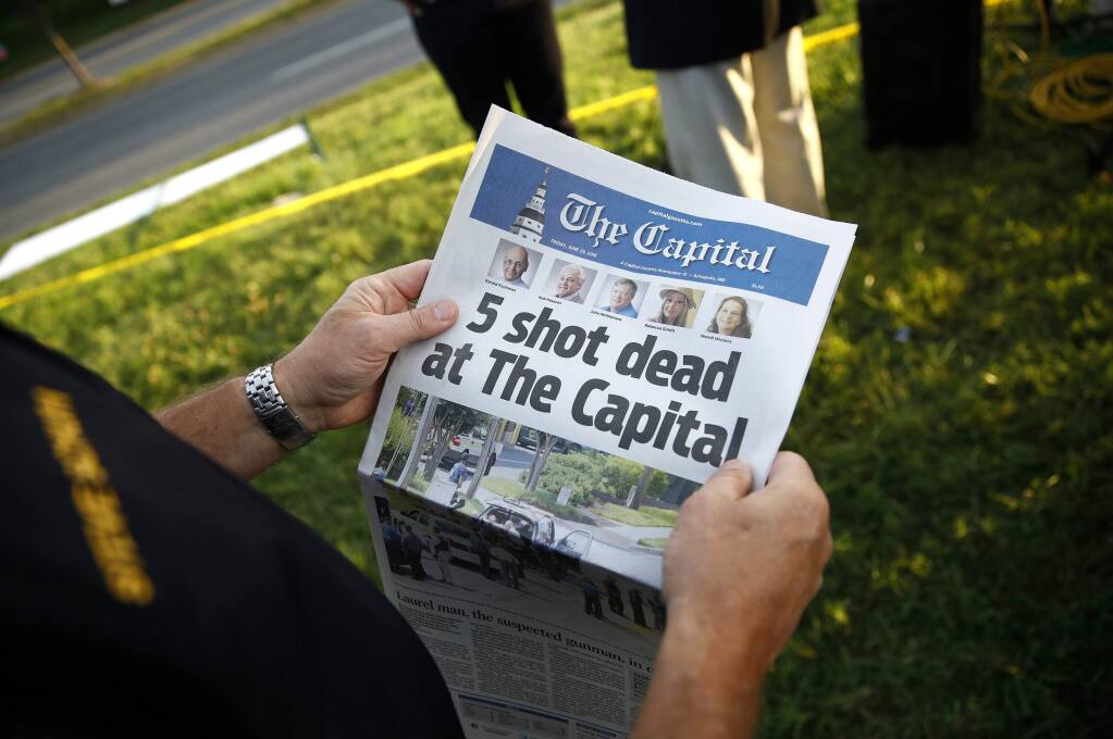 Steve Schuh, county executive of Anne Arundel County, holds a copy of The Capital Gazette near the scene of a shooting at the newspaper's office, Friday, June 29, 2018, in Annapolis, Md. (AP Photo/Patrick Semansky)