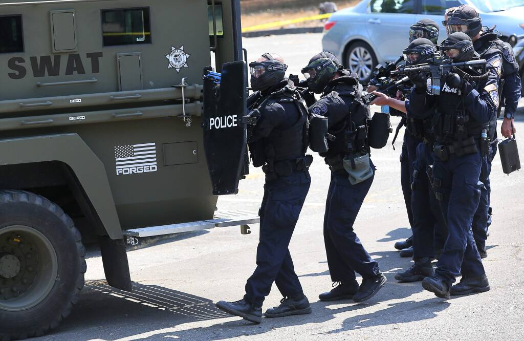 Members of the Santa Rosa Police Department SWAT team prepare to enter a building during a training simulation in Santa Rosa on Thursday, Aug. 10, 2017. (Christopher Chung / The Press Democrat)