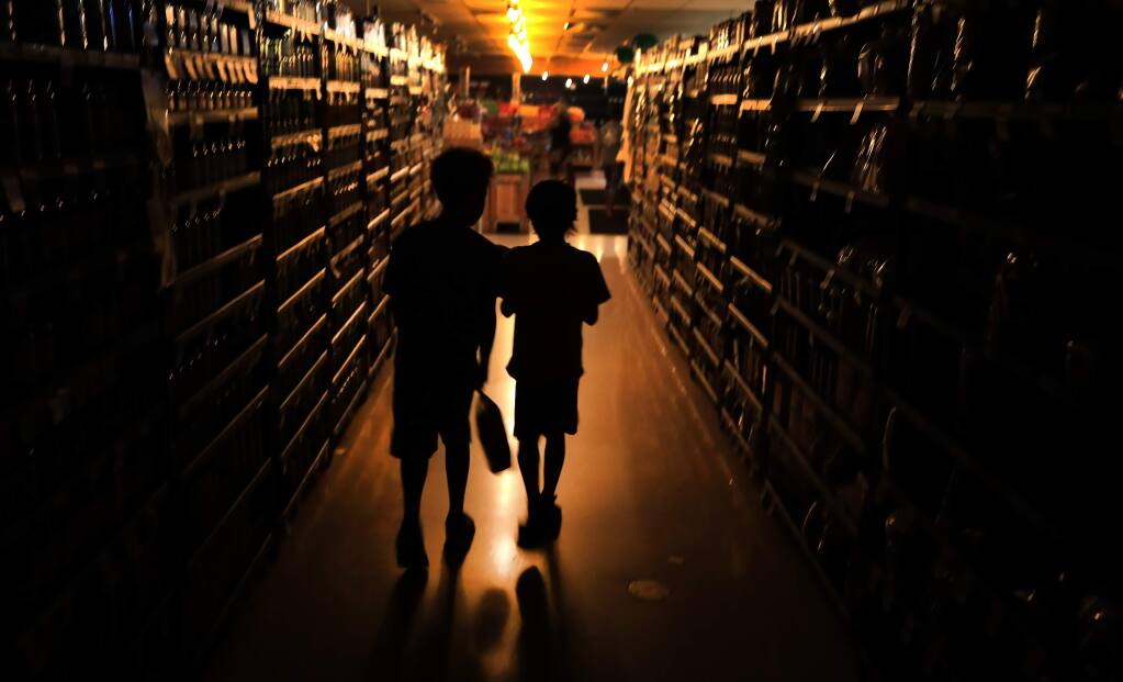 Elijah Carter, 11, left, and Robert Haralson, 12, help shop for their parents in a darkened Oliver's Supermarket in Rincon Valley, Wednesday, Oct. 23, 2019. The west side of the store was lit by patio lights powered by a generator as power was shut off again by PG&E due to fire danger. (Kent Porter / The Press Democrat)