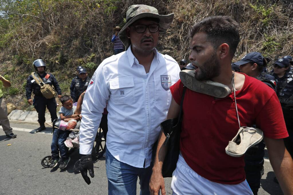 A Central American migrant, right, is taken into custody by a Mexican Federal Police agent on the highway to Pijijiapan, Mexico, Monday, April 22, 2019. Mexican police and immigration agents detained hundreds of Central American migrants Monday in the largest single raid on a migrant caravan since the groups started moving through Mexico last year. (AP Photo/Moises Castillo)