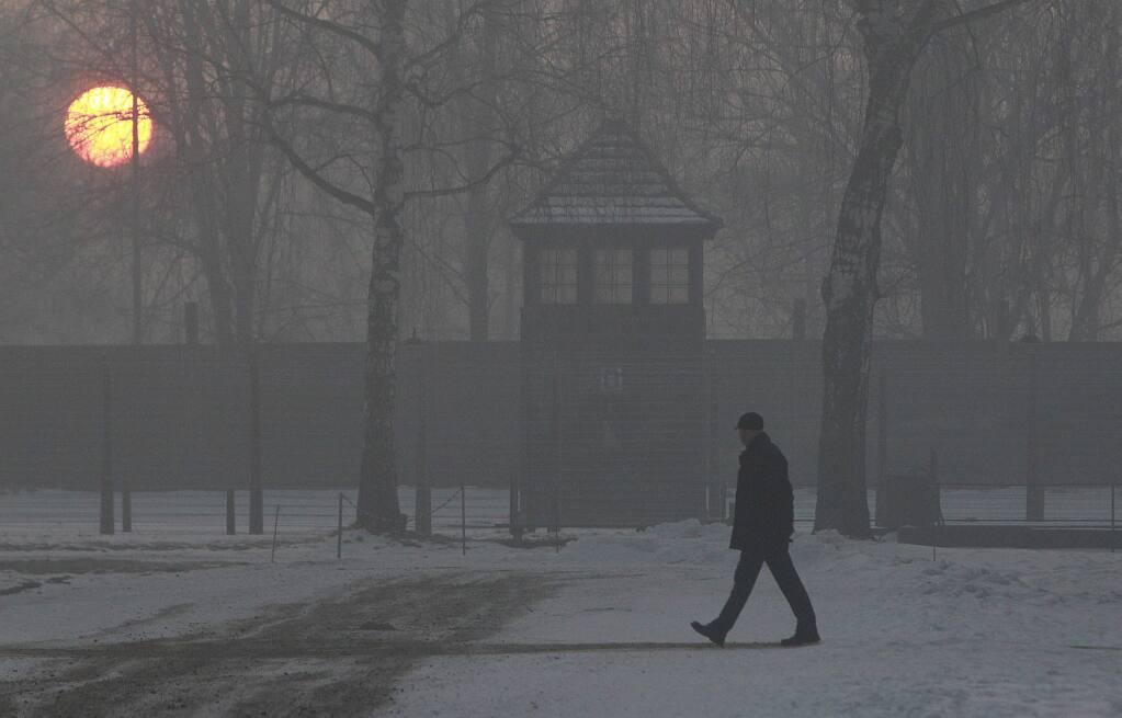 A man visits Auschwitz-Birkenau at sunrise on the 72nd anniversary of the liberation of the German death camp, in Oswiecim, Poland, Friday, Jan. 27, 2017. (AP Photo/Czarek Sokolowski)