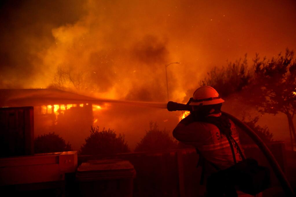 A Santa Rosa firefighter works to put out a house fire on Sansone Drive in Santa Rosa, on Monday, Oct. 9, 2017. (BETH SCHLANKER/ PD)