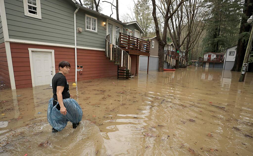 Chris Tipton looks for floating toys and personal belongings after Armstrong Creek flooded earlier this month in Guerneville. (KENT PORTER / The Press Democrat)