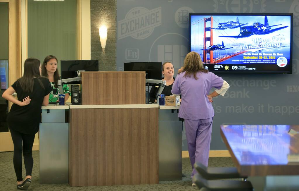PHOTO: 1 BY KENT PORTER/ THE PRESS DEMOCRAT-Exchange Bank employees Meegan Kamanaka, in green at left, and Caitlin Bradbury help customers at the remodeled Windsor branch.