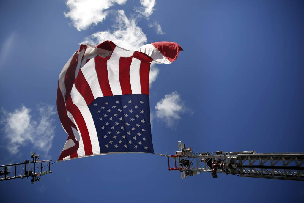 Firefighters hang a flag over the entrance to the Wells Fargo Center for the Arts before the 'Putting Out the Fire' concert on Sunday, Nov. 15, 2015 in Santa Rosa. (BETH SCHLANKER / The Press Democrat)