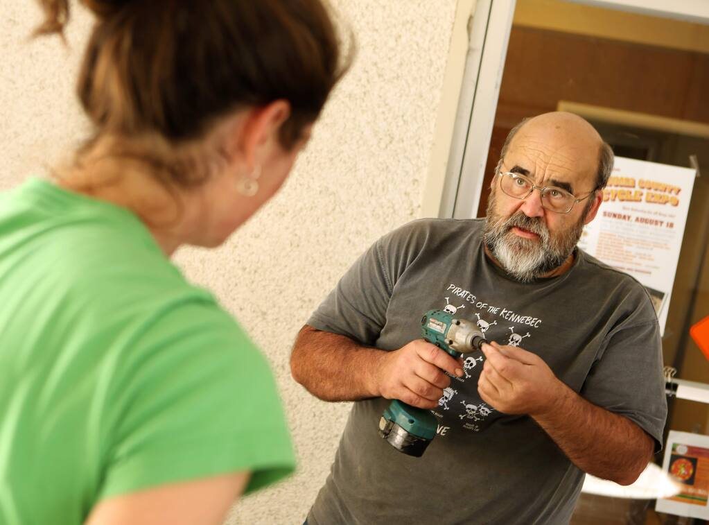 Gary Helfrich helps Aileen Carroll build a 'bicycle seesaw' for the Sonoma County Bicycle Expo on Friday, August 16, 2013. (Conner Jay/The Press Democrat)