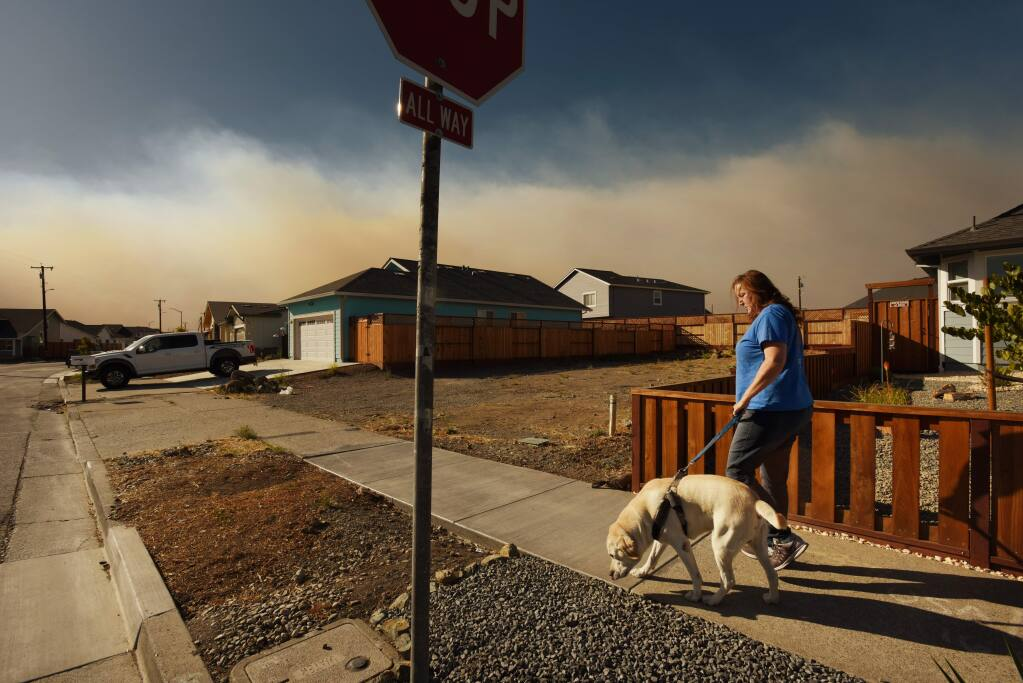 Tricia Woods walking her dog Jack towards her home on Hopper Avenue while a stream of thick smoke from the Kincade Fire flows just north of her Coffey Park neighborhood in Santa Rosa, California. Woods admits to sleeping poorly since the start of the Kincade Fire and of also having deep empathy for those currently losing their homes to the blaze. October 27, 2019.(Photo: Erik Castro/for The Press Democrat)