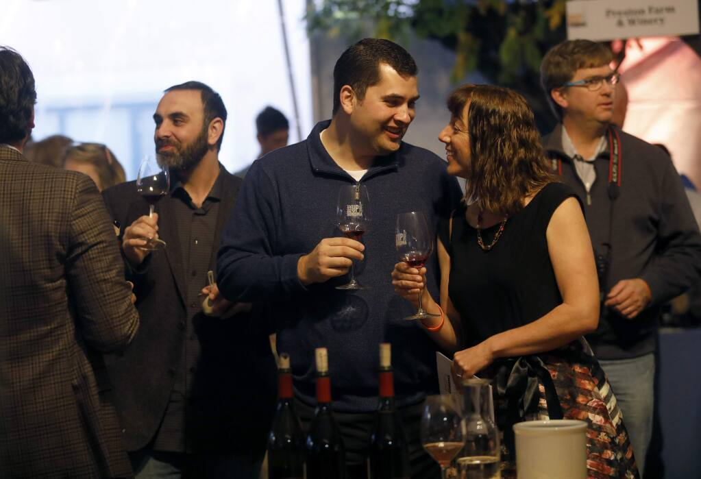 Jordan Burns and his wife Jennifer Branham-Burns enjoy a glass of wine during the RISE UP SONOMA culinary event at Sonoma Country Day School in Santa Rosa on Sunday, December 3, 2017. (BETH SCHLANKER/Press Democrat)